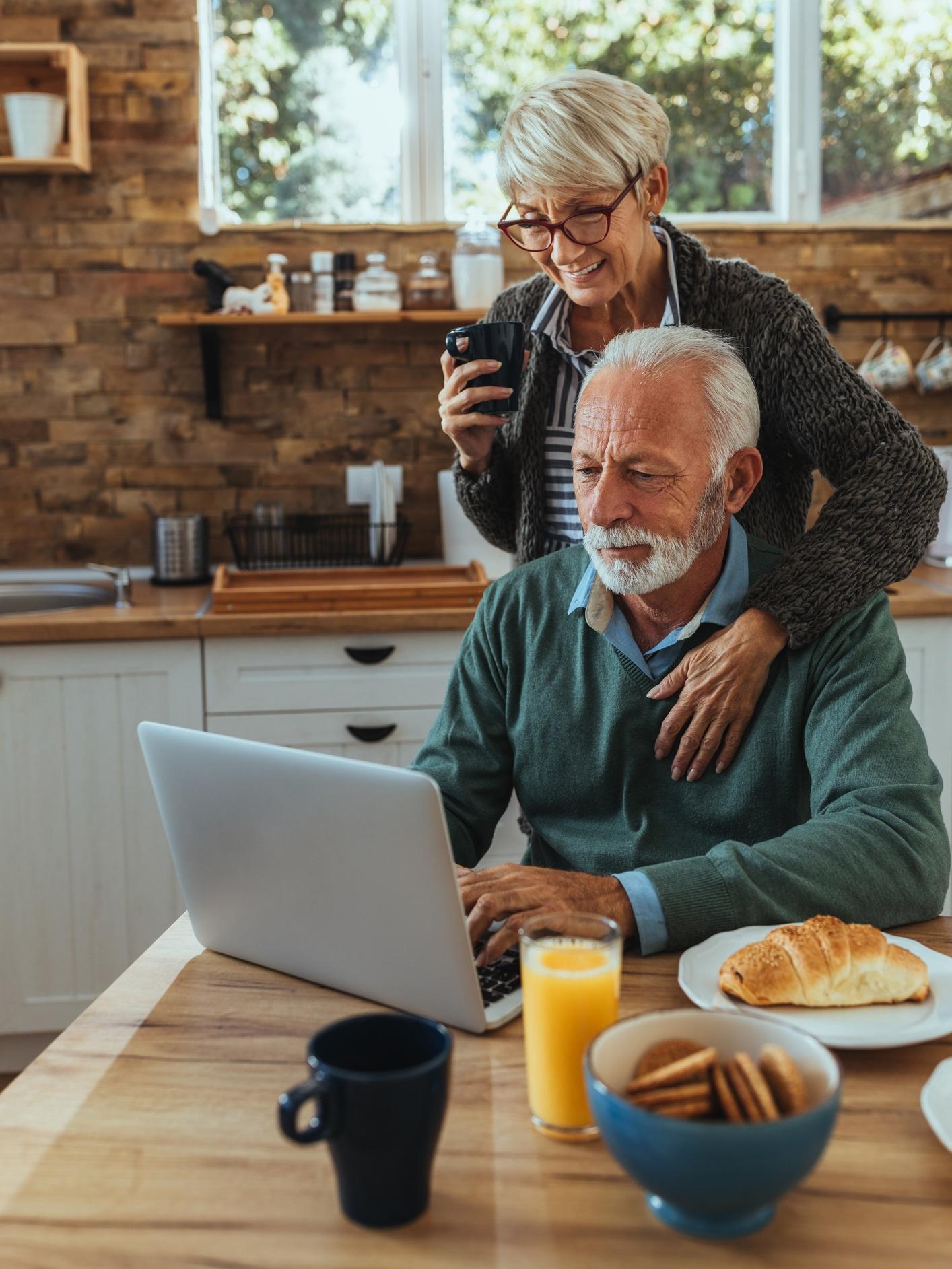 Sfeerbeeld: een ouder stel bekijkt iets op een laptop tijdens het ontbijt.